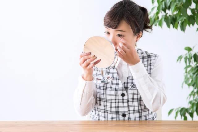 鏡でまつ毛を確認する女性のイメージ画像